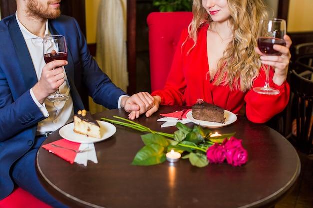 Giovani coppie che bevono vino e che tengono le mani al tavolo