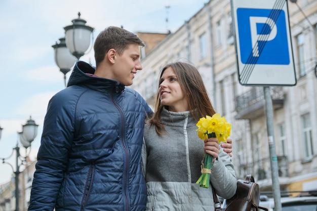 Giovani coppie che camminano con il mazzo dei fiori gialli della molla