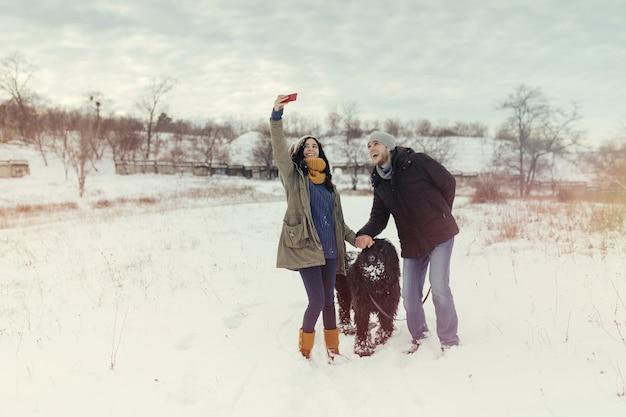 Giovani coppie che camminano con un cane in un giorno di inverno