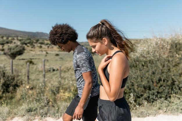 Giovani coppie che camminano mentre riposa durante la pratica corrente