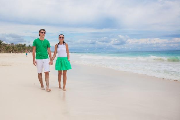 Giovani coppie che camminano sulla spiaggia esotica nel giorno soleggiato