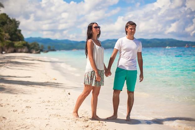 Giovani coppie che camminano sulla spiaggia sabbiosa vicino al mare