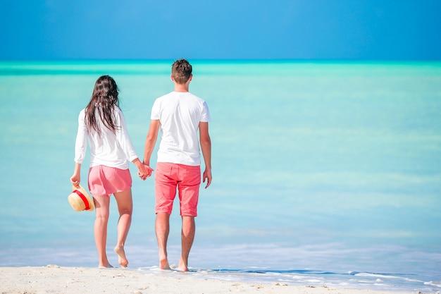 Giovani coppie che camminano sulla spiaggia tropicale