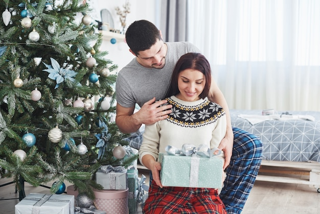 Giovani coppie che celebrano il natale. un uomo improvvisamente ha presentato un regalo a sua moglie.