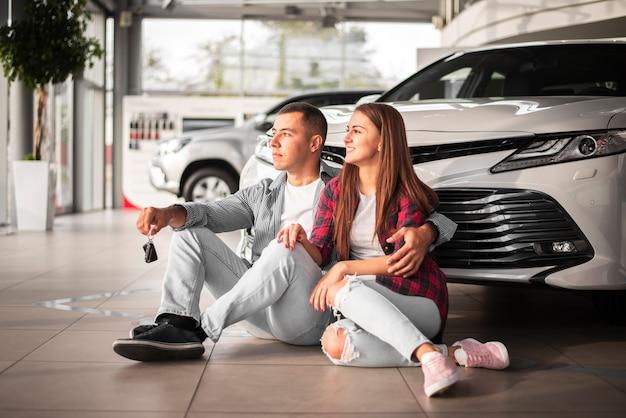 Giovani coppie che celebrano nuova auto