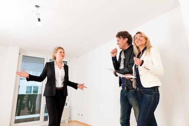 Giovani coppie che cercano bene immobile con l'agente immobiliare femminile