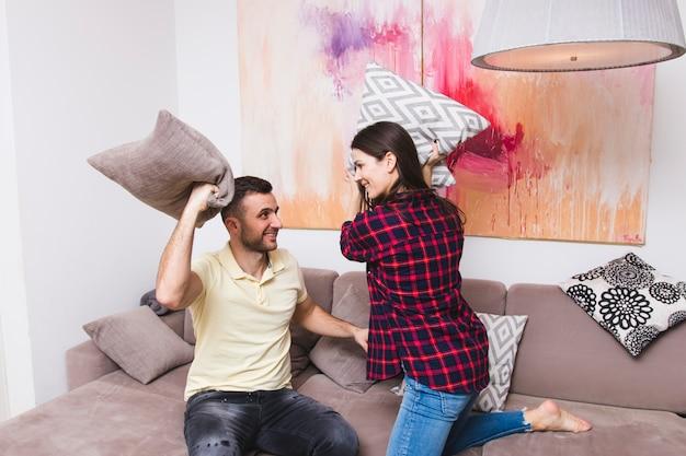 Giovani coppie che combattono con il cuscino a casa