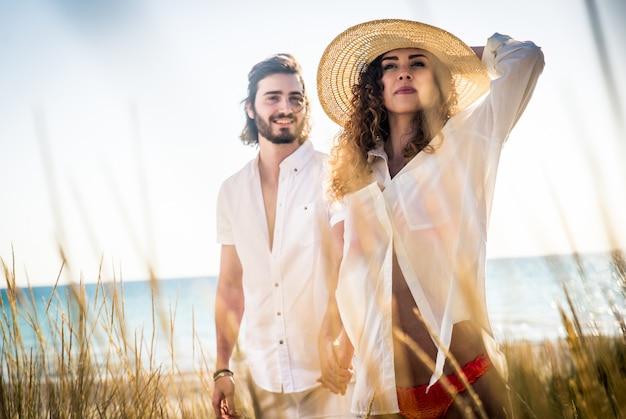 Giovani coppie che condividono l'umore felice e amore sulla spiaggia