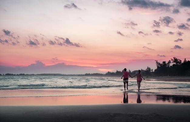 Giovani coppie che corrono lungo la spiaggia al tramonto, tramonto tropicale sull'isola