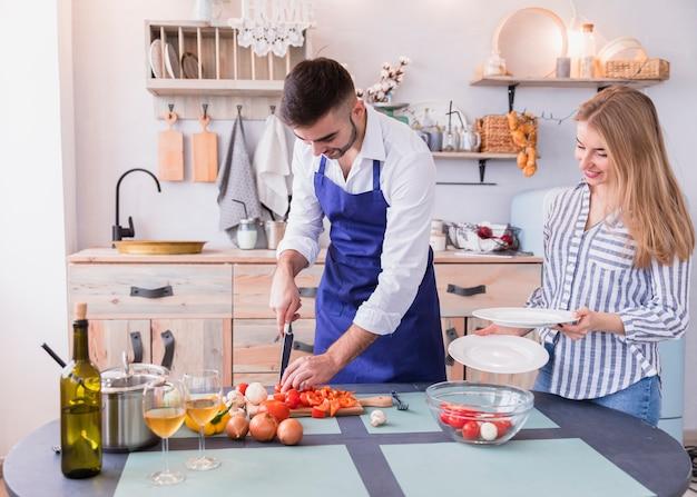 Giovani coppie che cucinano insalata in cucina