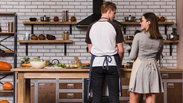 Giovani coppie che cucinano nella cucina accogliente