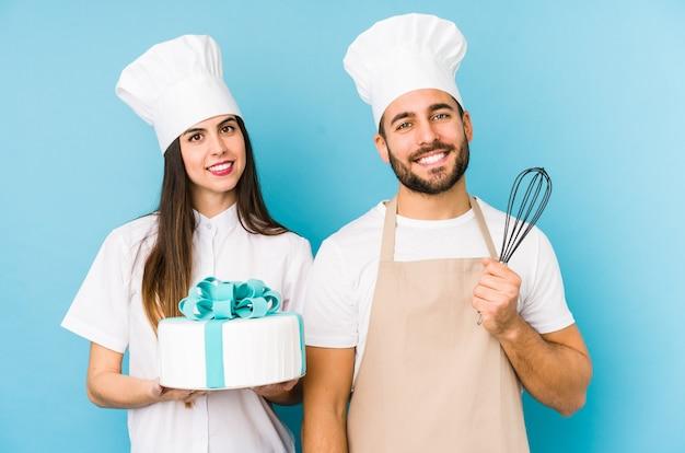 Giovani coppie che cucinano una torta che tocca insieme parte posteriore della testa