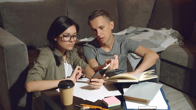 Giovani coppie che discutono di un progetto comune o della progettazione di un nuovo appartamento che lavora insieme seduti sul pavimento a casa