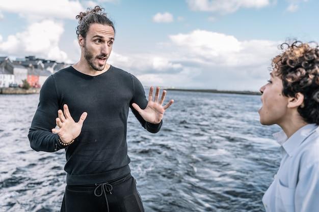 Giovani coppie che discutono espressamente con il mare sfocato