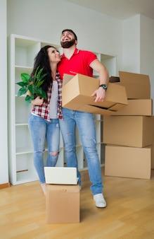 Giovani coppie che disimballano le scatole di cartone a nuova casa