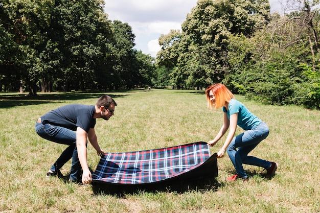 Giovani coppie che dispongono coperta sull'erba verde nel parco