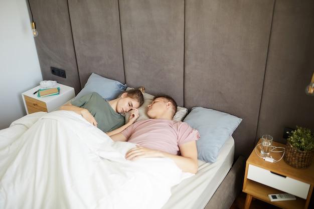 Giovani coppie che dormono pacificamente a letto sotto la coperta bianca