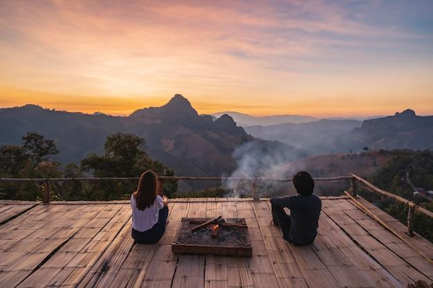 Giovani coppie che esaminano il bellissimo tramonto sulla montagna