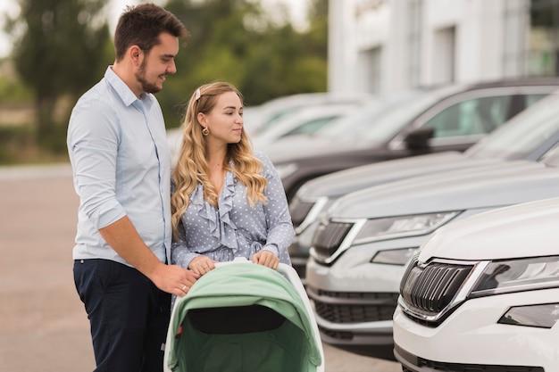 Giovani coppie che esaminano le automobili