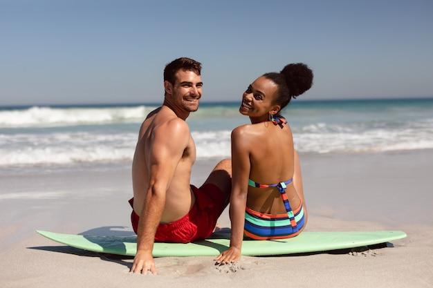 Giovani coppie che esaminano macchina fotografica mentre sedendosi sulla tavola da surf alla spiaggia sotto il sole