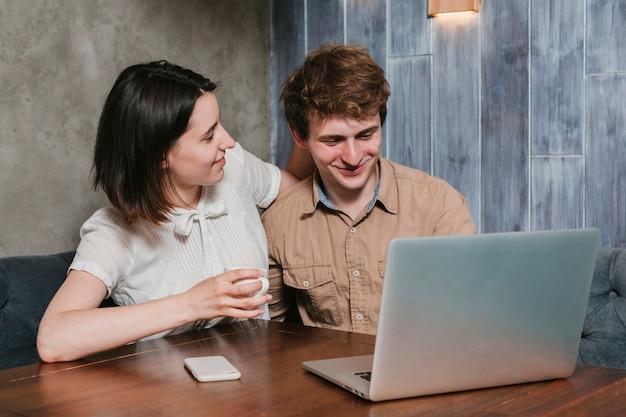 Giovani coppie che esaminano sorridere del computer portatile