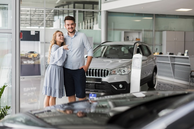 Giovani coppie che esaminano un'automobile