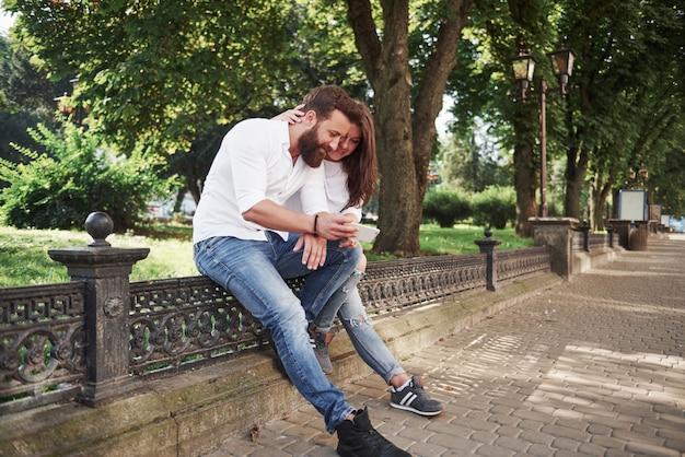 Giovani coppie che esaminano uno smartphone un giorno soleggiato nella città