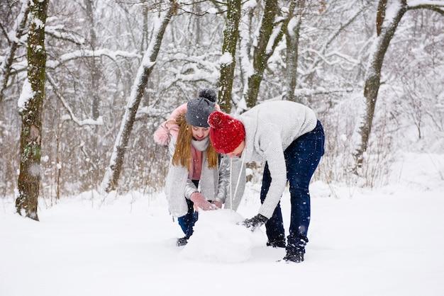 Giovani coppie che fanno pupazzo di neve in foresta
