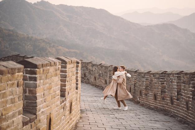 Giovani coppie che funzionano e che volteggiano alla grande muraglia della cina