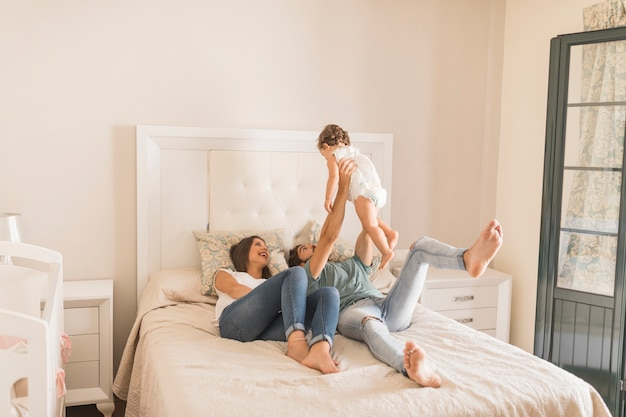 Giovani coppie che giocano con la figlia sul letto