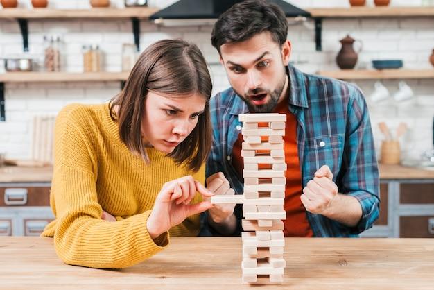 Giovani coppie che giocano il blocco impilato di legno sul tavolo