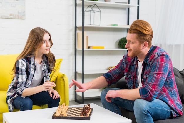 Giovani coppie che giocano il gioco degli scacchi a casa