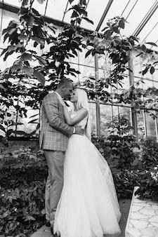Giovani coppie che godono dei momenti romantici mentre camminano nel parco. sposa e sposo alla moda che posano e che baciano nel parco il giorno delle nozze. sposa elegante in bellissimo abito bianco, sposo in un abito.