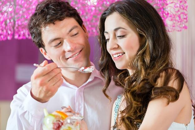 Giovani coppie che godono del loro tempo nella gelateria