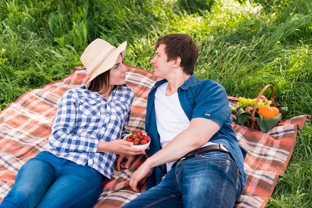 Giovani coppie che godono del tempo di picnic nella foresta