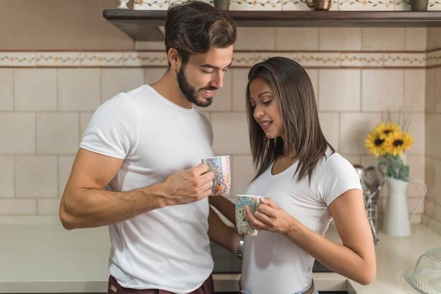 Giovani coppie che godono della bevanda calda in cucina