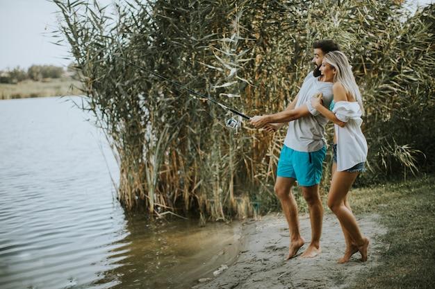 Giovani coppie che godono della pesca il giorno soleggiato in un lago calmo