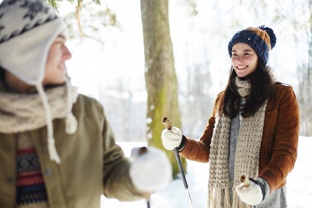 Giovani coppie che godono di sciare