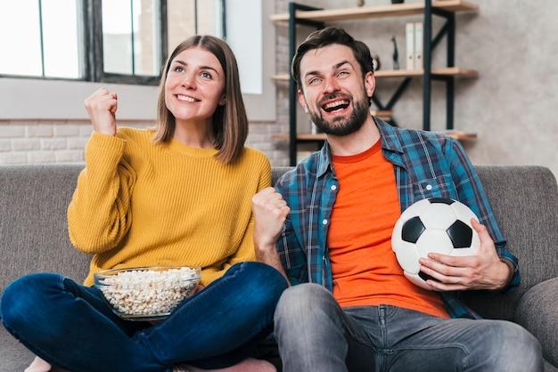 Giovani coppie che guardano il gioco di calcio che incoraggia dopo la conquista