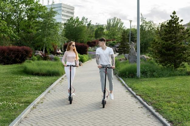 Giovani coppie che guidano uno scooter elettrico nel parco