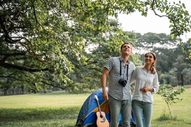 Giovani coppie che hanno divertimento con la chitarra su picnic e campeggio nel parco