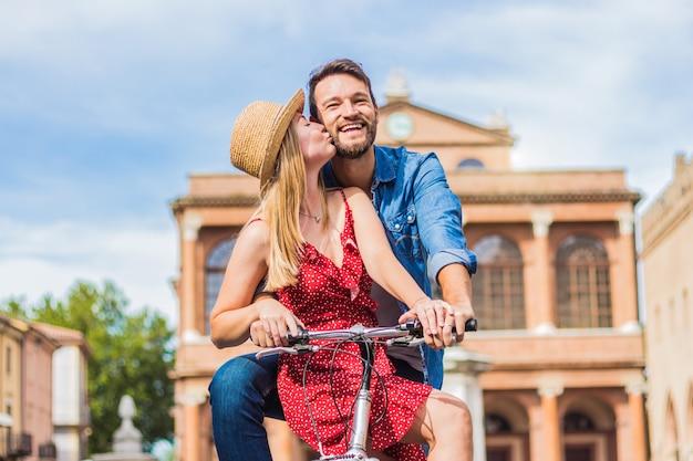 Giovani coppie che hanno divertimento in città andando a fare un giro in bicicletta in vacanza