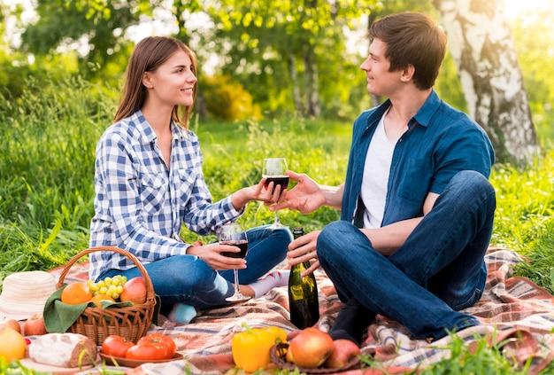 Giovani coppie che hanno picnic con cibo e vino