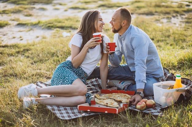 Giovani coppie che hanno picnic con pizza in parco