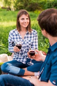 Giovani coppie che hanno picnic e che tengono i bicchieri di vino