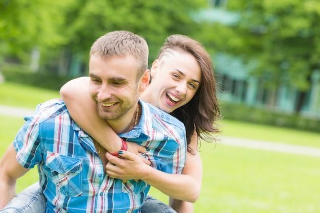 Giovani coppie che hanno piggyback ride