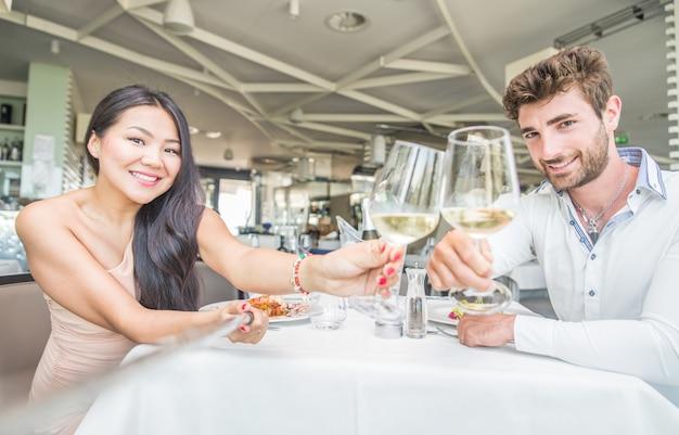 Giovani coppie che hanno pranzo romantico in un ristorante elegante