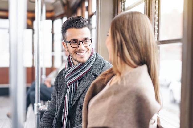 Giovani coppie che hanno una conversazione mentre sedendosi all'interno del trasporto del tram d'annata