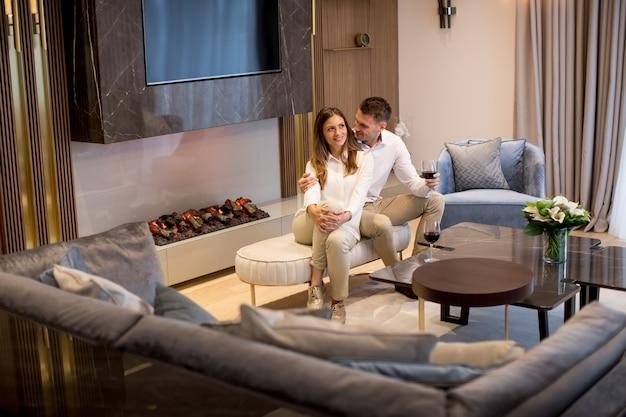 Giovani coppie che hanno una serata romantica con un bicchiere di vino rosso a casa nel salotto contemporaneo