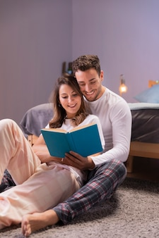 Giovani coppie che leggono insieme a letto